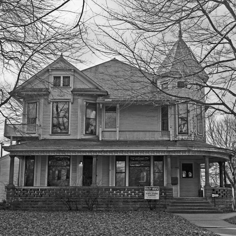 Black and white image of the Foley House, a large, Victorian style house with a wraparound porch.