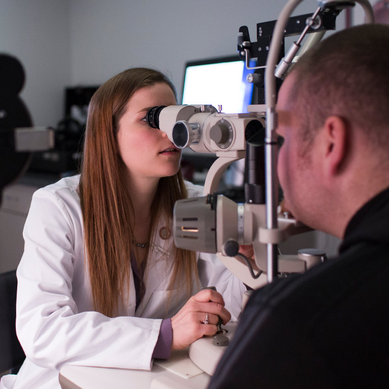 A female optometry student in a white jacket examines a patient's eyes.