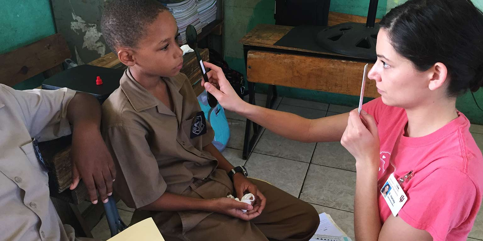 A student volunteer performs an eye exam on a young boy in Frome, Jamaica.