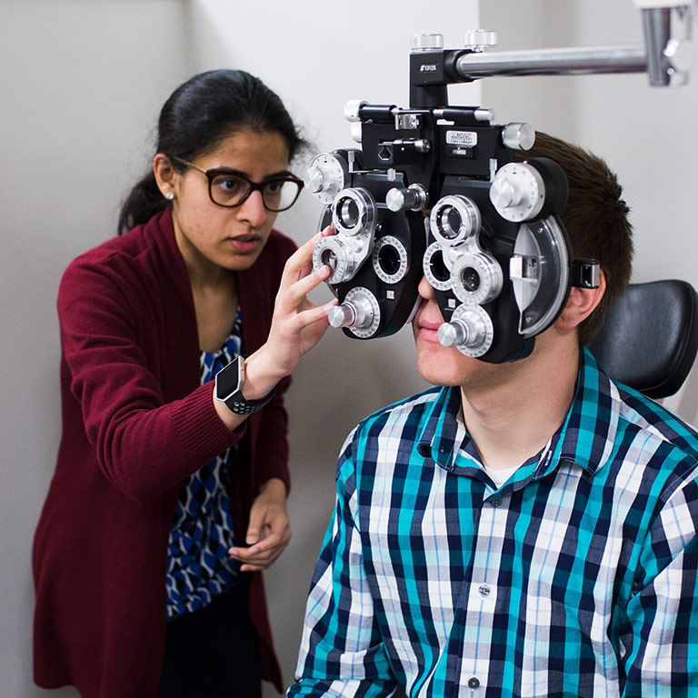 Optometry students practice giving eye exams.