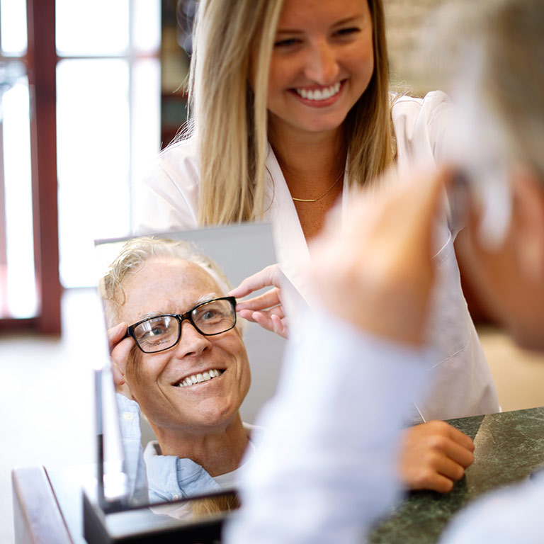 A male customer tries on a pair of black rimmed glasses at the Atwater Eye Care Center. He is looking in the mirror while being helped by a female staff member.