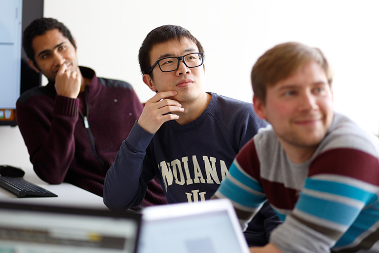 Three male students in a classroom setting