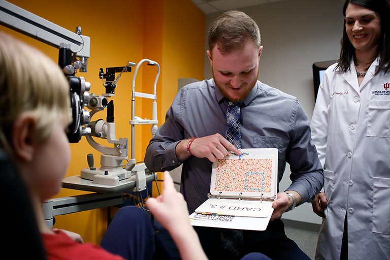 A male optometry student in shirt and tie holds up a binder of colored dot designs. The patient, a six-year-old boy, points to the page.