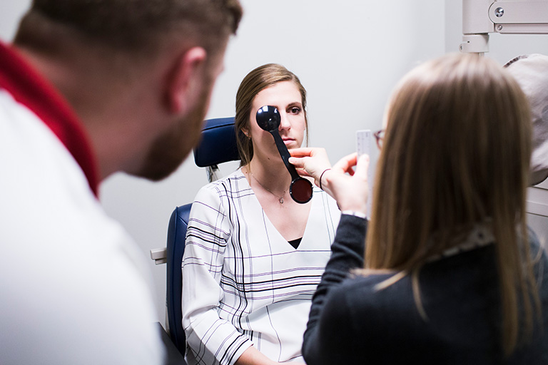 Two optometry students perform an eye exam on a female patient.