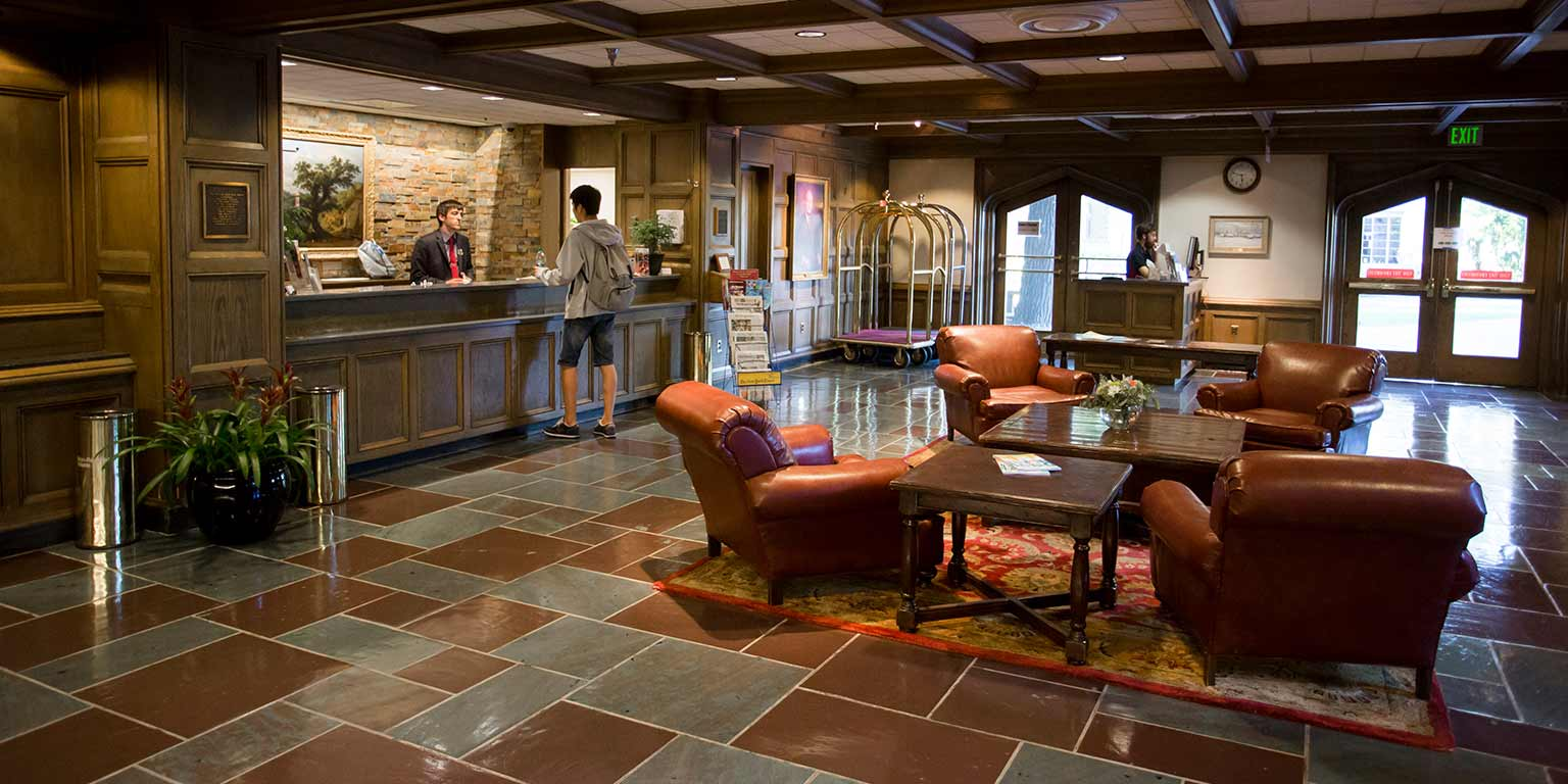 The front lobby of the Biddle Hotel has a seating area with four plush leather seats and a concierge desk.