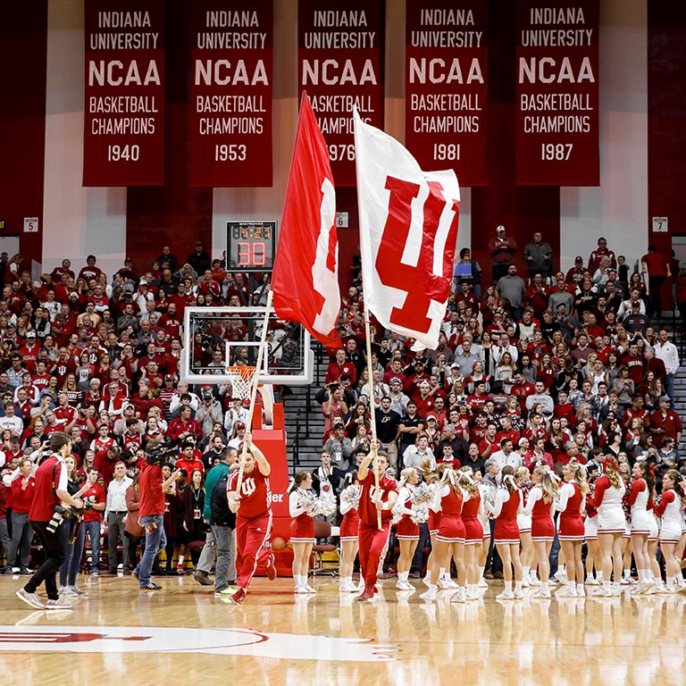 Male and female cheerleaders run IU flags on the court at Assembly Hall.