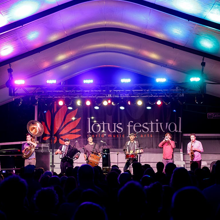 A band with a tuba, accordion, drum, and other instruments play on a brightly lit stage at the Lotus Festival.