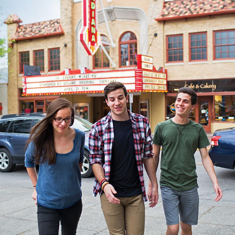 A group of three students walk from the Buskirk Chumley Theatre in downtown Bloomington.