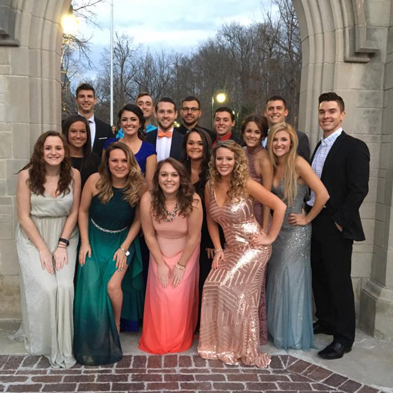A large group of optometry students pose for a photo wearing formal attire.