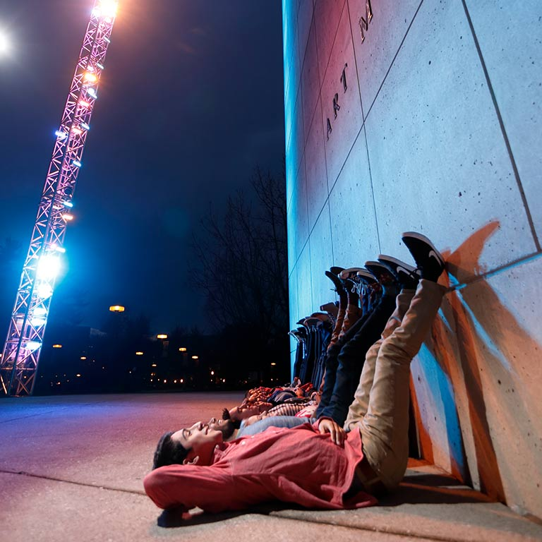 A diverse group of students lay on the ground in front of the art museum, lit by the famous Light Totem.
