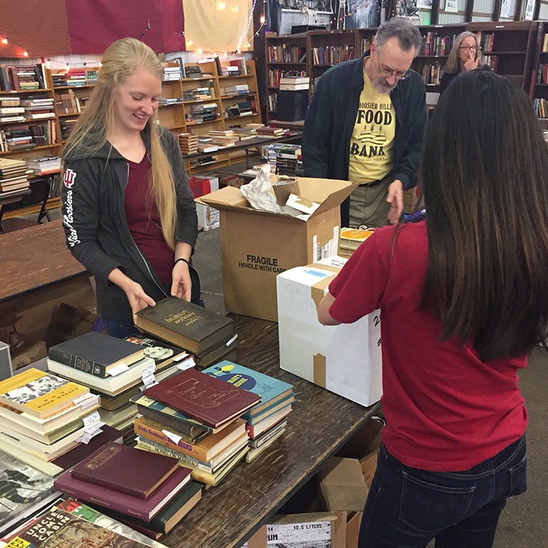 Optometry students in the Honor Society pack boxes with books.