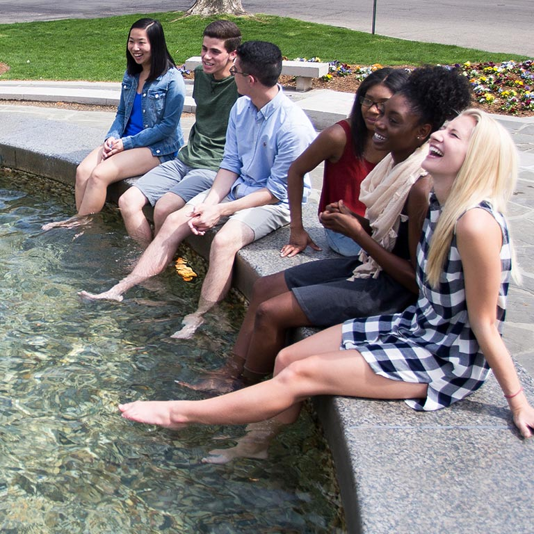 A diverse group of students dip their feet in Showalter Fountain.