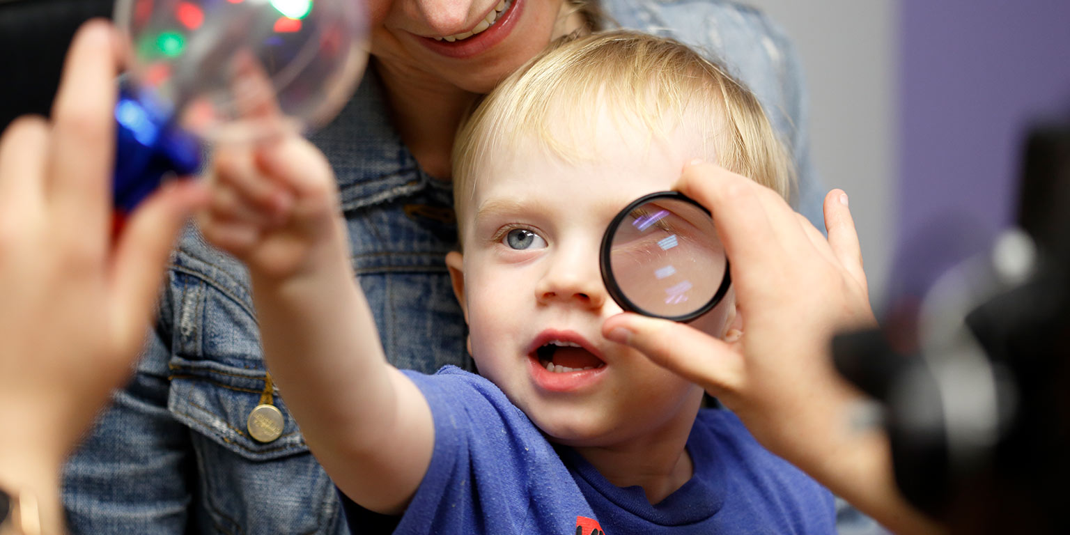 An infant looks at a brightly colored toy while an optometry student examines his eye