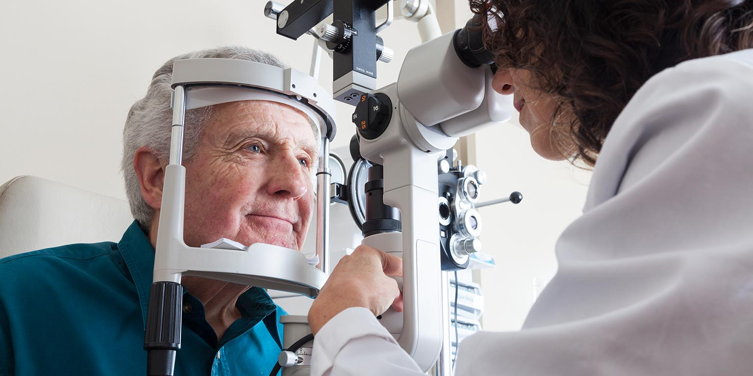 An optometry student uses a split lamp to examine an elderly patient's eyes.