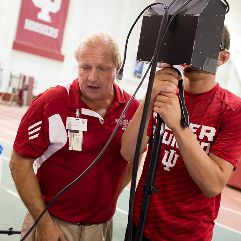 Nicholas Port assists a student athlete in using his concussion detecting device.